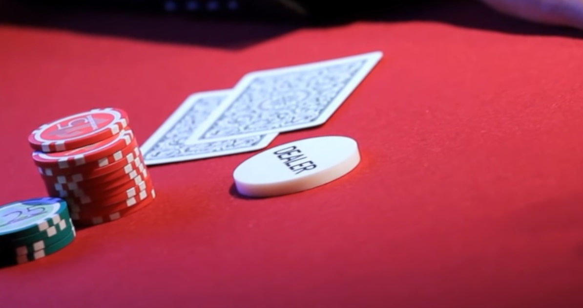 A poker player's face-down hole cards, two stacks of chips, and the dealer button on a  red felt table.