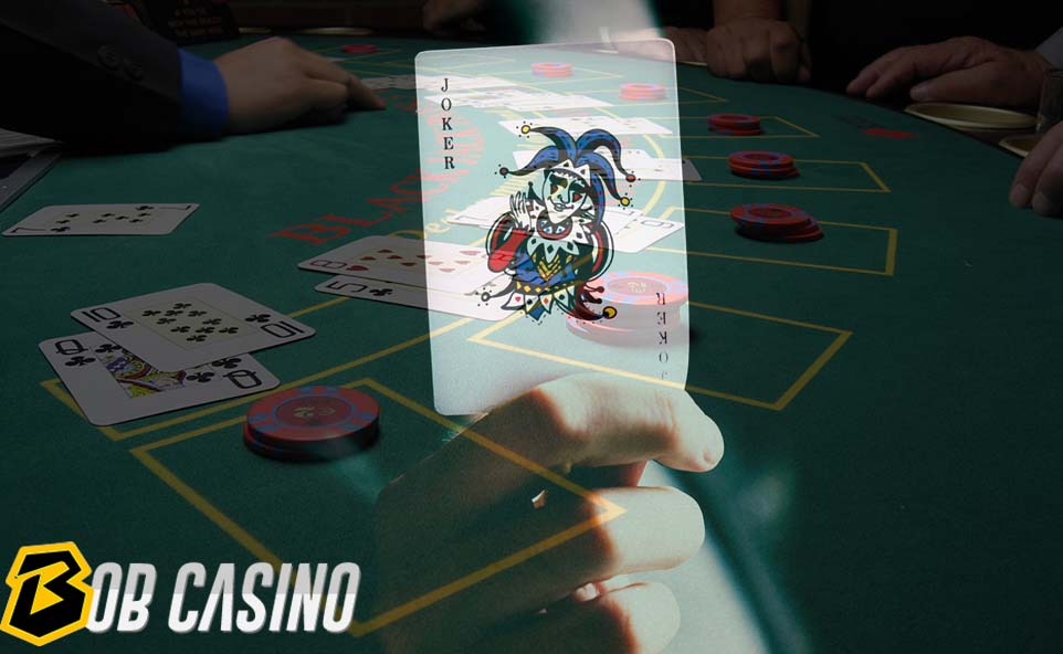 Man holding joker card in hand while playing poker