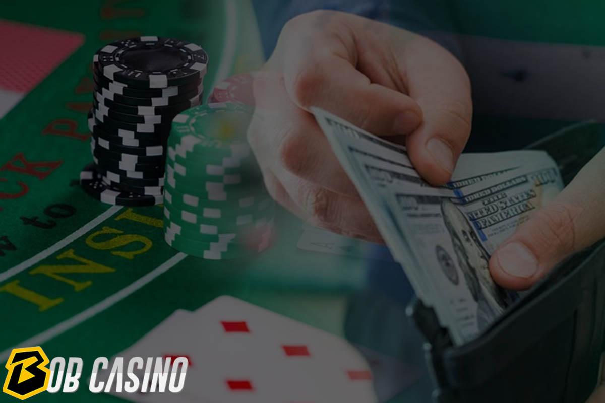 man holding 100 dollar banknotes making wager in poker