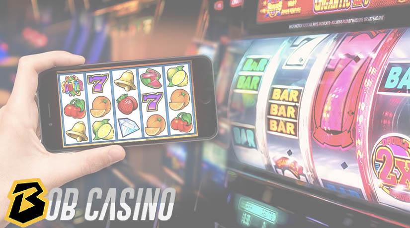 Slot online di ponsel dekat gulungan slot mekanik.